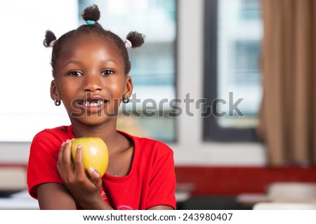 African girl at school desk ready to eat her apple. - stock photo