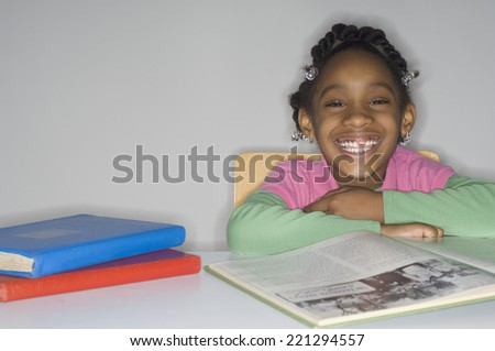 African girl at table with school books - stock photo