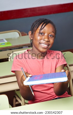 African girl holding school book in elementary school class - stock photo