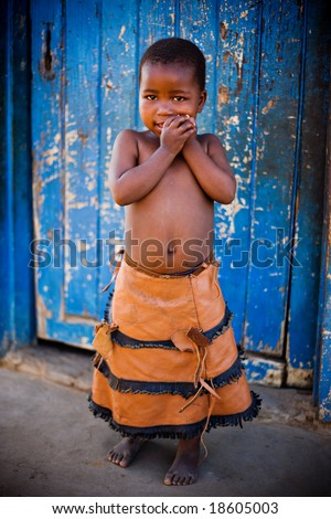 african girl in front of a blue door, vignette added for a dramatic effect. - stock photo