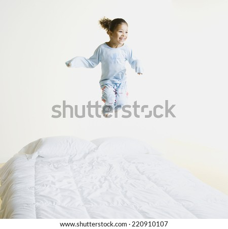 African girl jumping on bed - stock photo