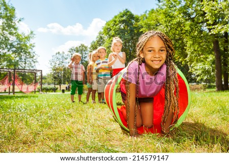 African girl play crawling through tube in park - stock photo