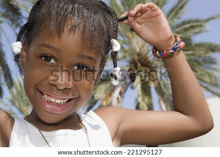 African girl pulling on braid - stock photo