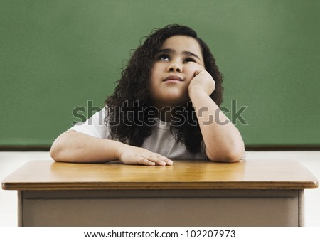 African girl sitting at school desk - stock photo