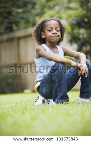 African girl sitting on soccer ball - stock photo