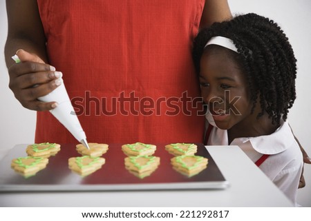 African girl watching mother decorate cookies - stock photo
