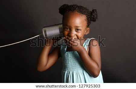 African girl with a tin and string on her ear - stock photo