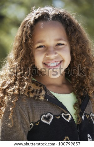 African girl with braces smiling outdoors - stock photo