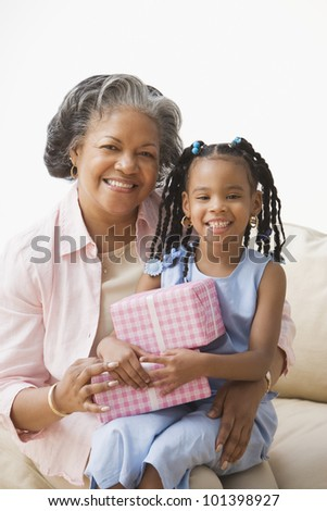 African grandmother and granddaughter hugging - stock photo