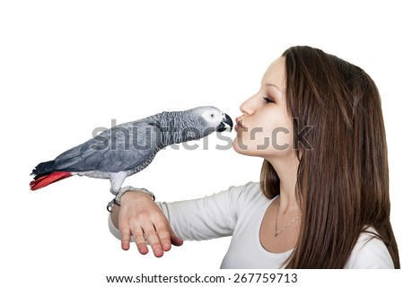 African gray parrot sitting on a girls hand  and kissing her on the lips. Isolated on white. - stock photo