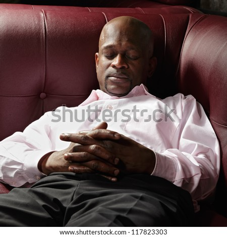 African guy having nap on red leather sofa - stock photo