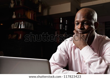 African guy in pink shirt sitting at laptop - stock photo