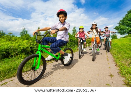 African guy rides bike with friends riding behind - stock photo