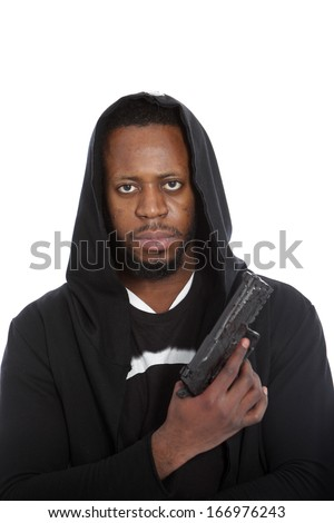 African hooligan or gangster wearing a black hooded top with a gun in his hand looking grimly at the camera in a threatening stance, isolated on white - stock photo