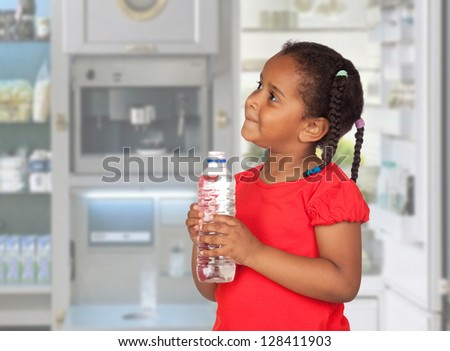 African little girl with water bottle in the kitchen - stock photo