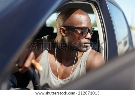 African male model in his car. Stylish young man with hands on steering wheel. Muscular young wearing sunglasses looking away. - stock photo