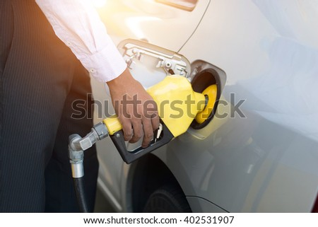 african male pumping gas at station - stock photo