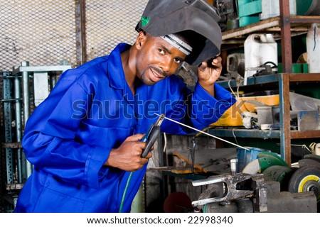 african male welder with welding equipment - stock photo