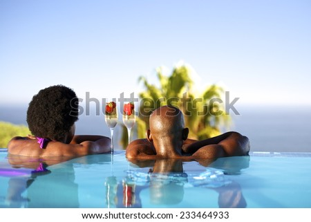 African man and woman in an infinity edge pool over looking the ocean. - stock photo