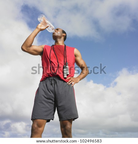 African man drinking from water bottle - stock photo