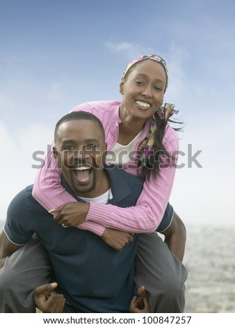 African man giving woman piggy back ride outdoors - stock photo