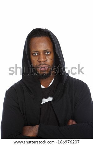 African man in a black hooded top staring directly at the camera with a grim serious expression and folded arms, upper body on white - stock photo