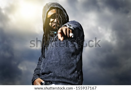 african man in hoodie pointing at camera - stock photo
