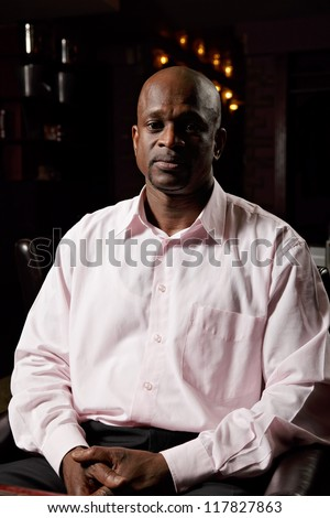 African man in pink shirt sitting in chair hands folded - stock photo