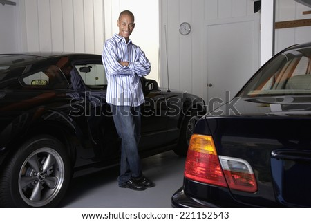 African man leaning on car - stock photo