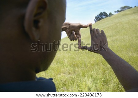 African man making frame with hands outdoors - stock photo