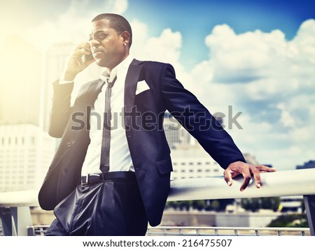 african man on smartphone in suit; - stock photo