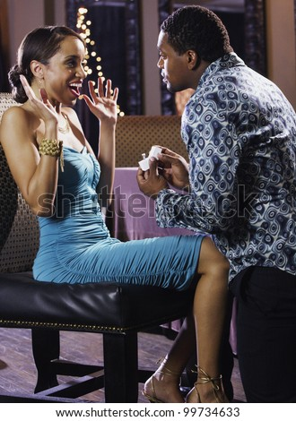 African man proposing to girlfriend with engagement ring - stock photo