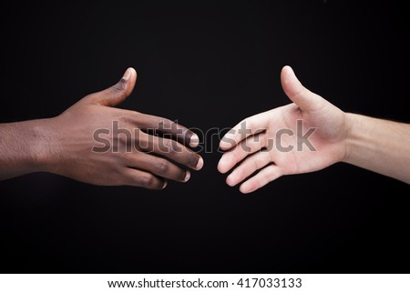 African man's hand shaking white man's hand on black background - stock photo