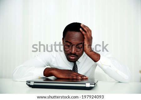 African man sleeping at his workplace in office - stock photo