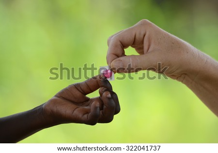 African Medicine Symbol. White woman gives medicine pill to native African girl, in Bamako, Mali. Unfortunately, in Africa there are lots of diseases like malaria, pneumonia, AIDS or simple Diarrhea. - stock photo