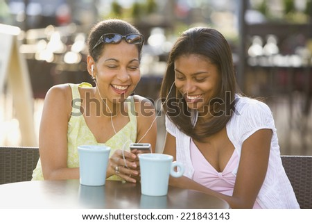 African mother and daughter listening to mp3 player - stock photo
