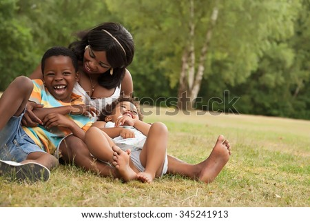 African mother and her kids are having fun in the nature - stock photo