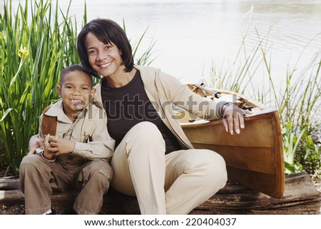 African mother and young son smiling next to canoe - stock photo