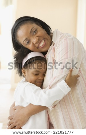 African mother hugging daughter - stock photo