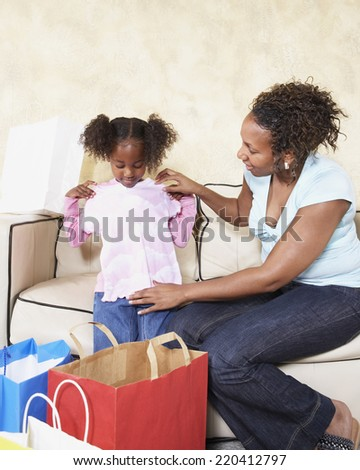 African mother showing young daughter new clothes - stock photo