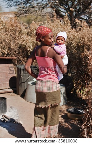African mother with baby girl, going to the summer kitchen, location Mmankgodi village , Botswana - stock photo