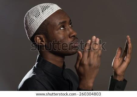 African Muslim Man Making Traditional Prayer To God While Wearing A Traditional Cap Dishdasha - stock photo