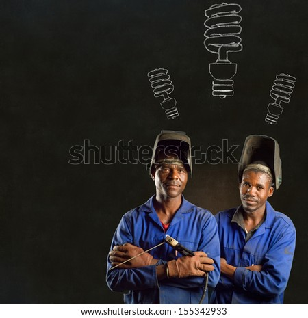 African or American black men industrial workers with chalk energy saving lightbulbs on blackboard background - stock photo