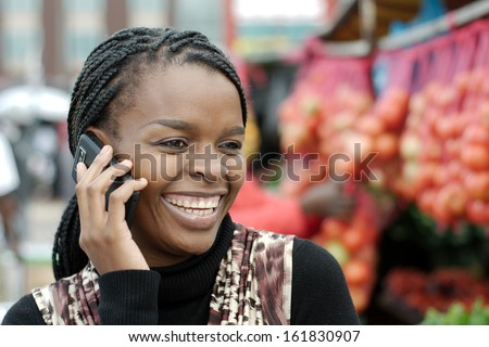 African or black American woman calling on mobile cellphone telephone in Alexandra township - stock photo