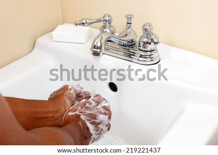 African person washing hands with soapy water - stock photo