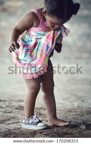 African poverty toddler with one shoe  standing in rural area cute portrait - stock photo