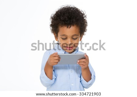 african schoolboy using smartphone against white background - stock photo