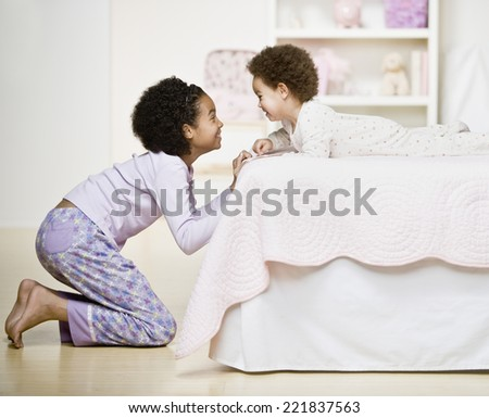 African sisters smiling at each other - stock photo