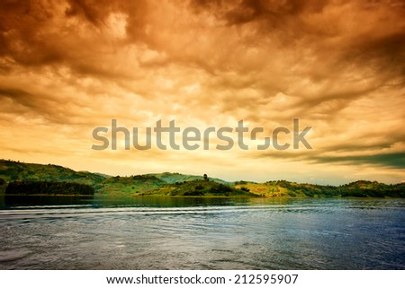 African sunset with stormy sky at Lake Bunyonyi in Uganda, Africa - stock photo