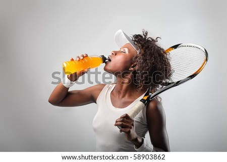 African tennis player drinking energy drink - stock photo